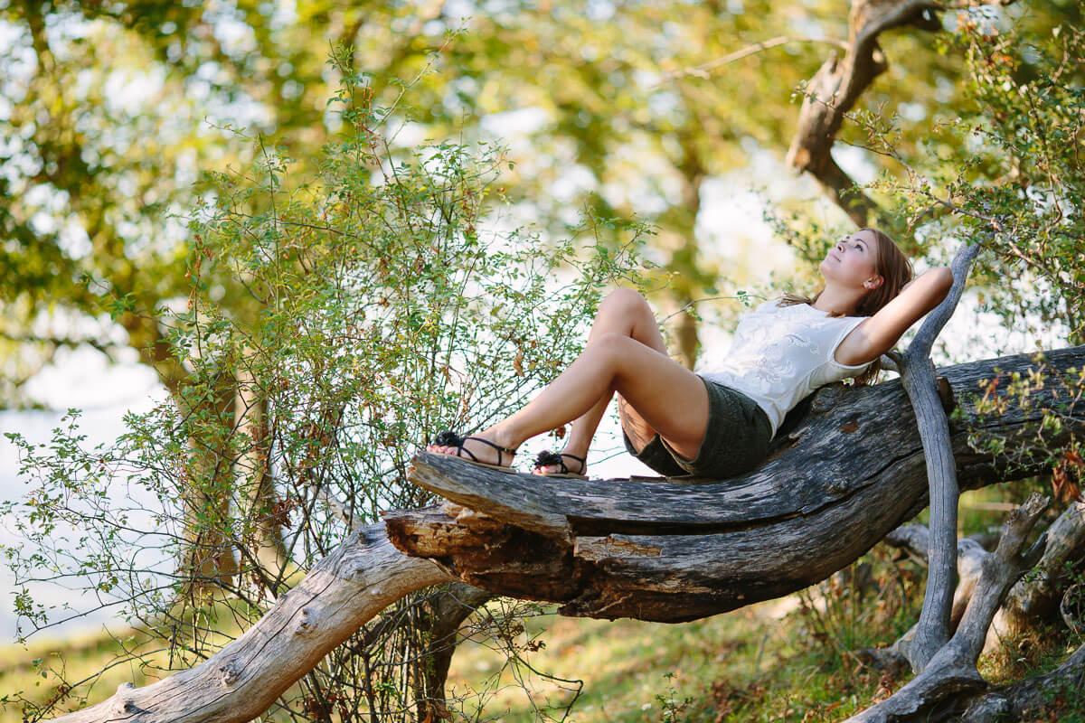 Frau liegt auf Baumstamm