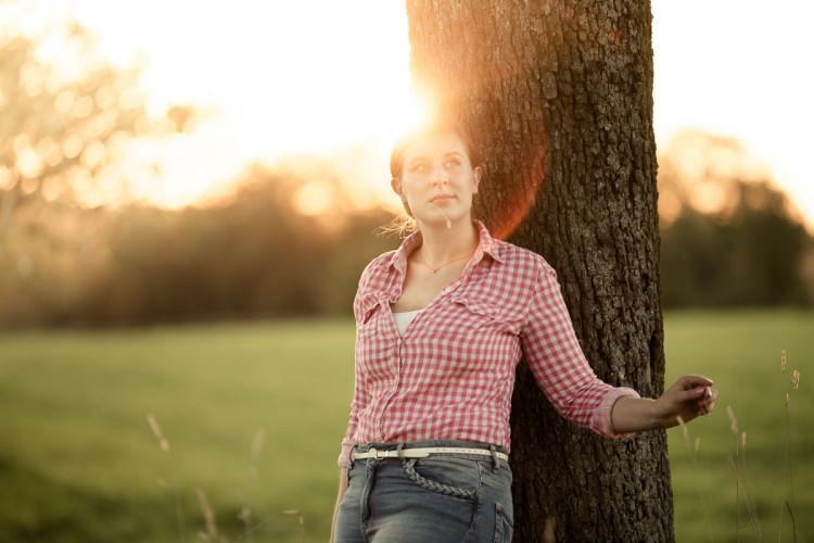 Frau lehnt an Baumstamm, Strohhalm im Mund, Sonne im Hintergrund