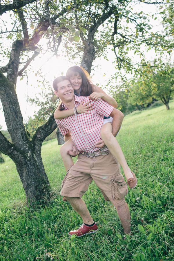 Paar läuft Huckepack auf Obstbaumwiese
