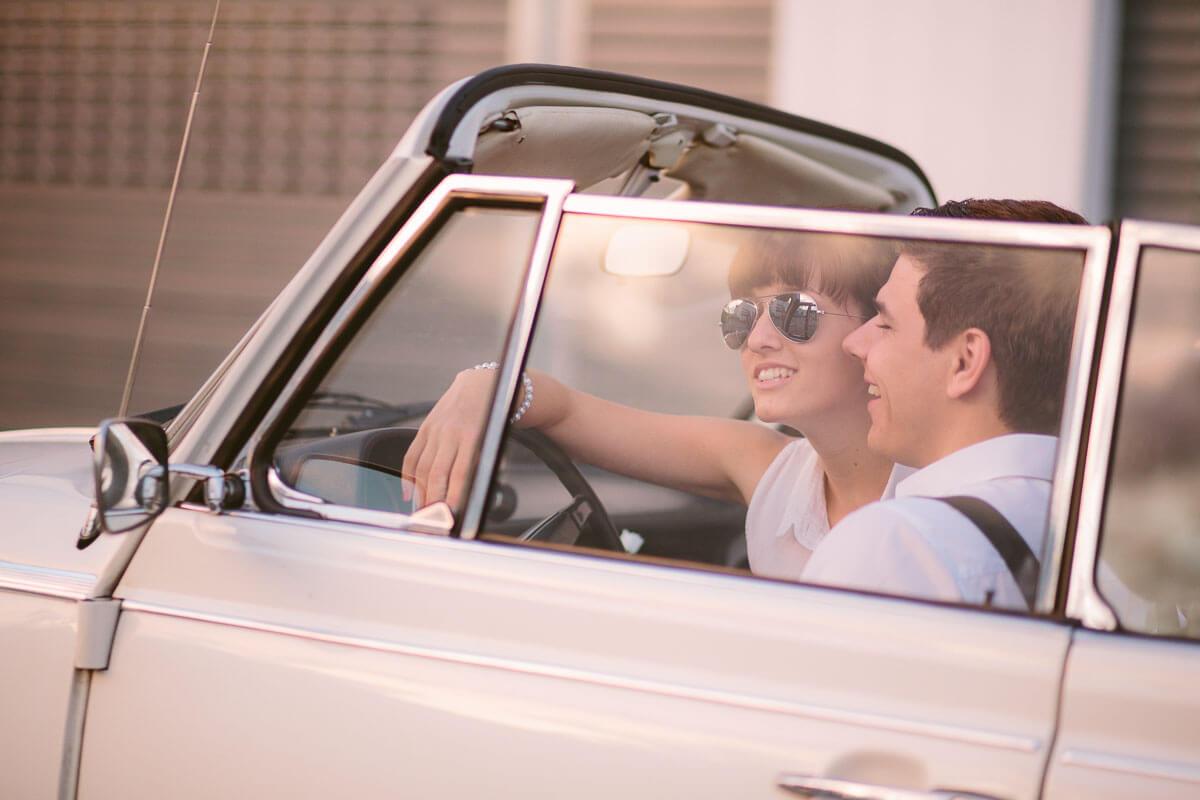 Paar sitzt in VW Käfter Cabrio, beide lachen