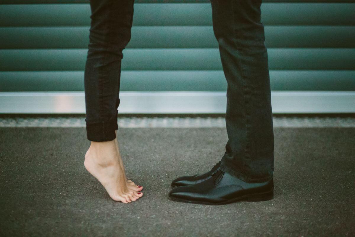 Barfuß auf Zehenspitzen und Lederschuhe