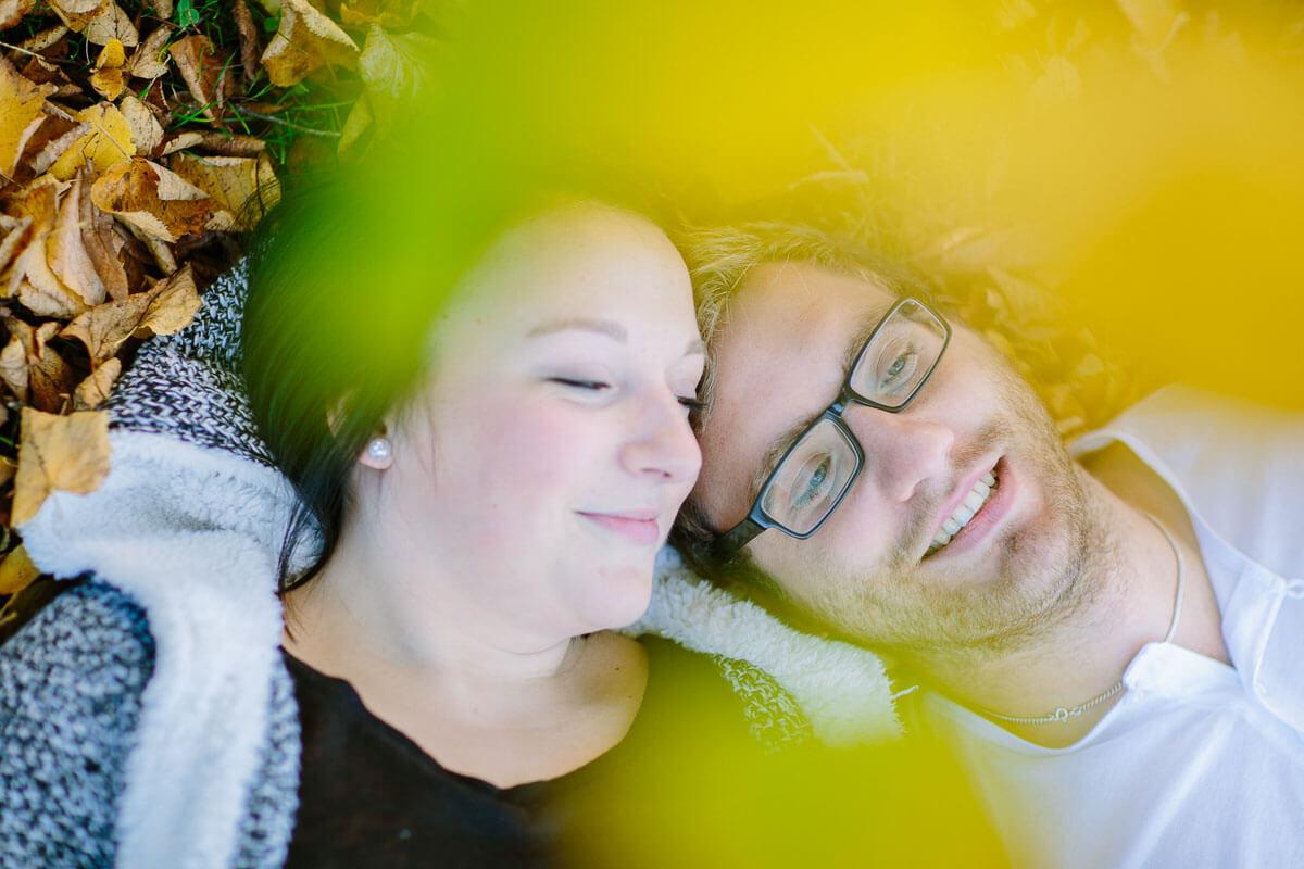 Paar liegt im Laub, Herbst