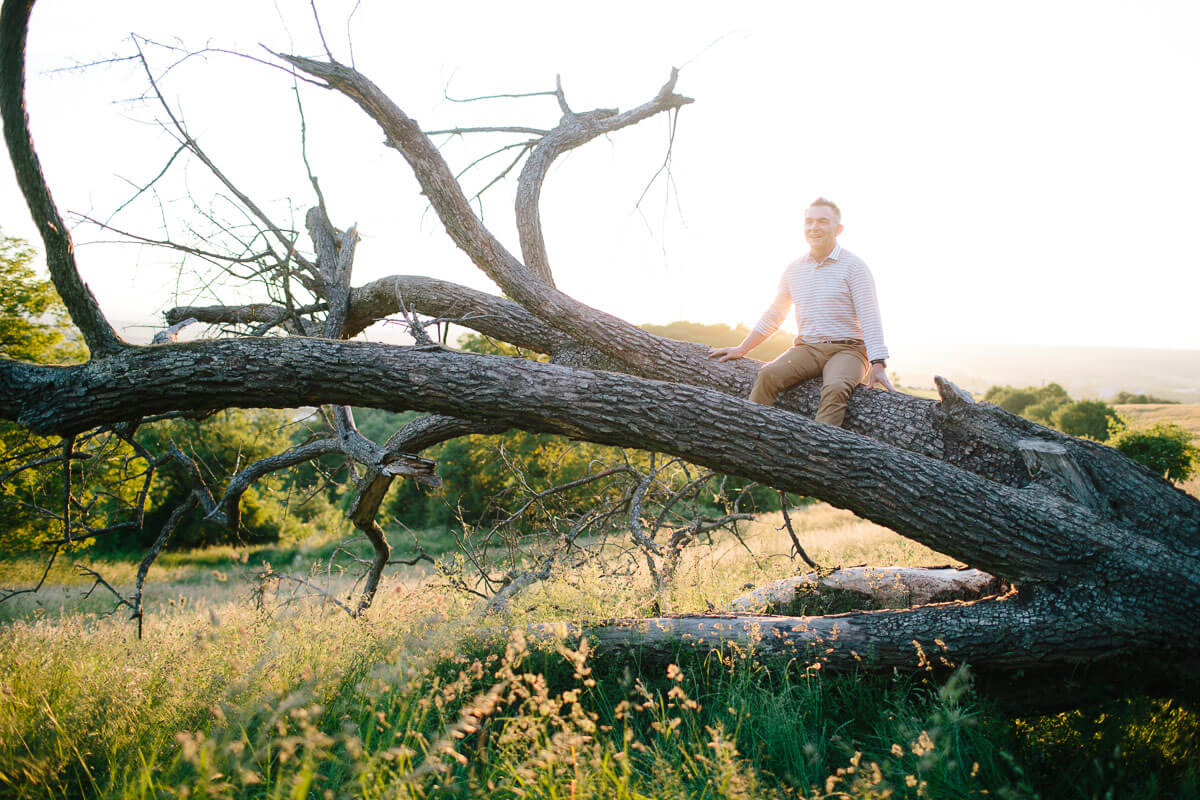 Mann sitzt auf Baumstamm, Sonne im Hintergrund