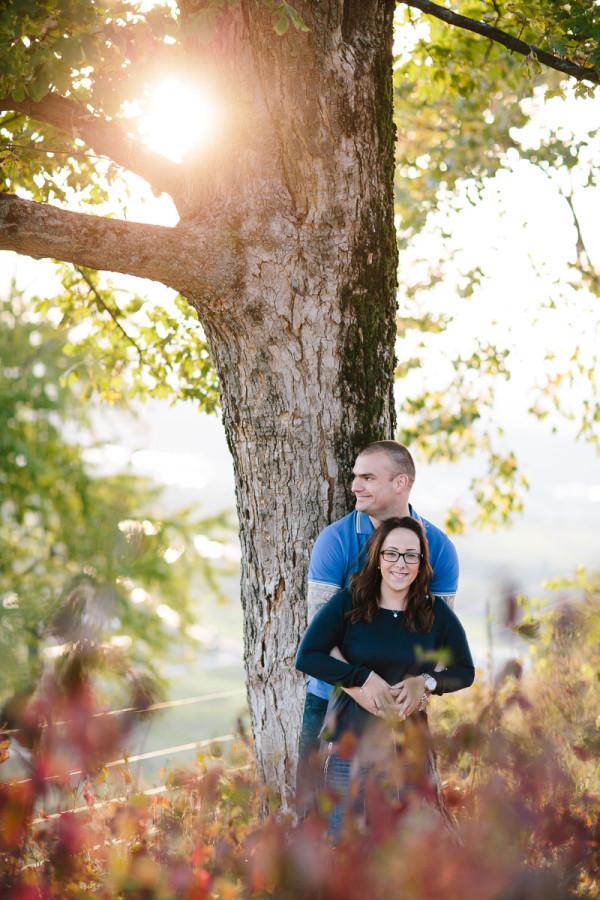 Paar steht an Baum gelehnt, Herbst