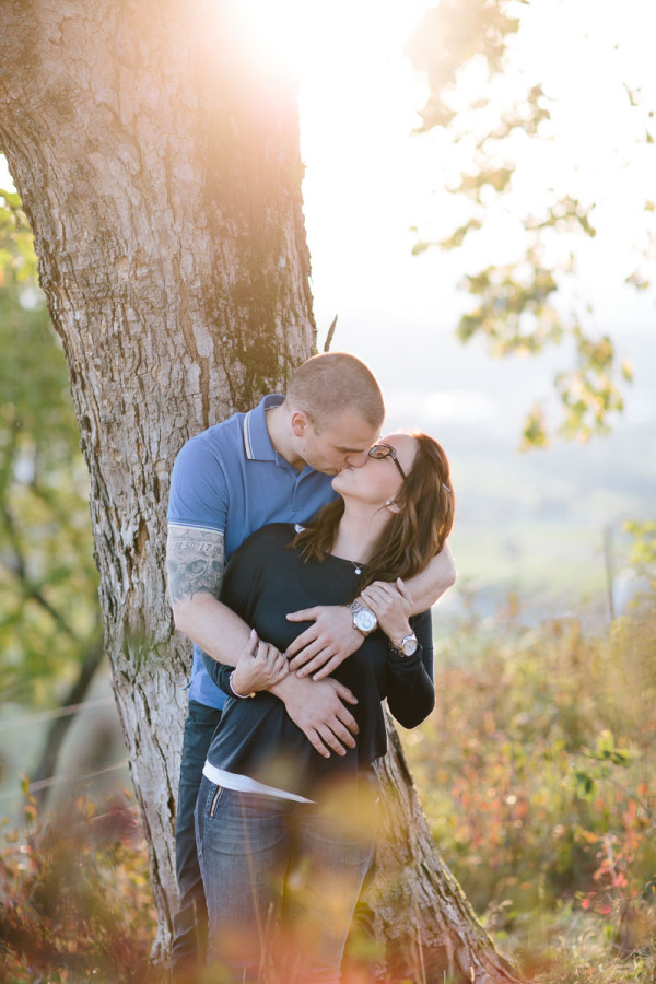 Paar steht küssend an Baum gelehnt, Herbst
