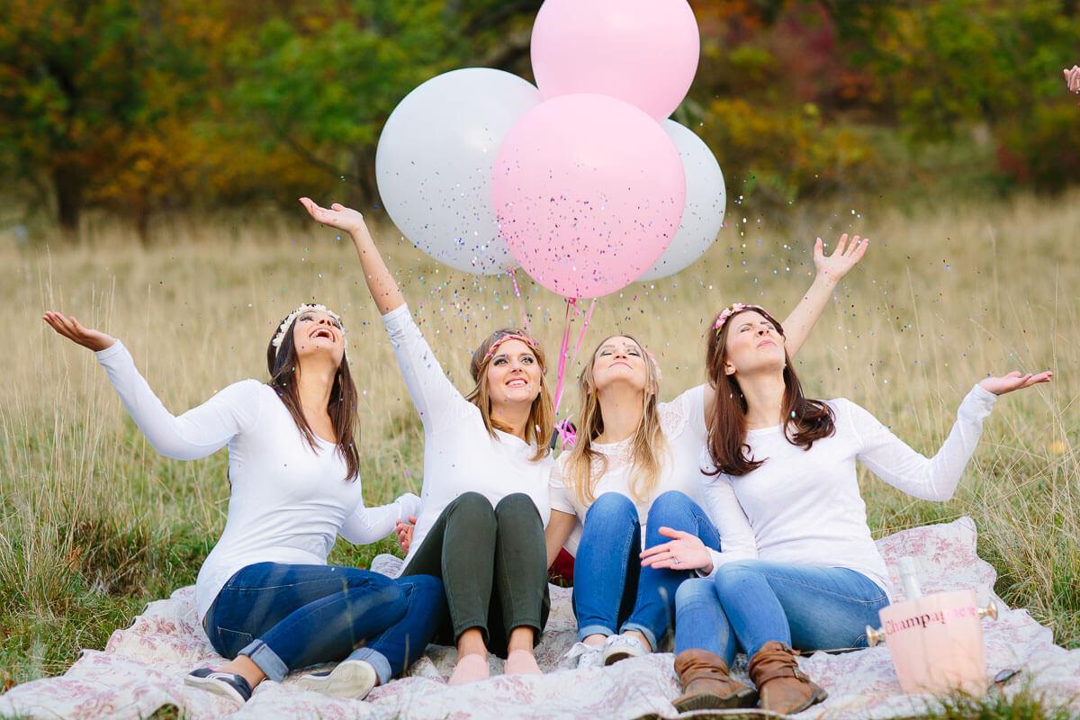4 Frauen sitzen auf einer Decke mit Luftballons und Konfetti