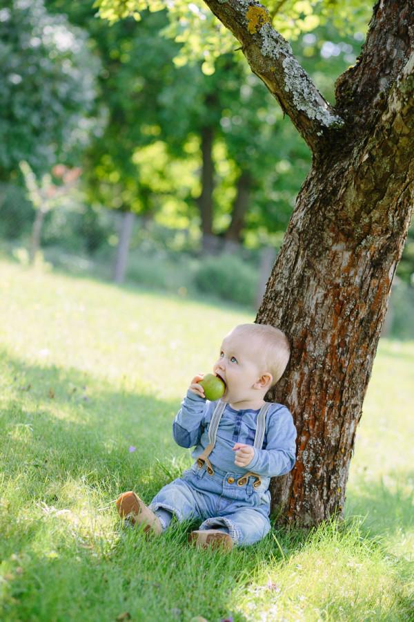 Kind sitzt an Baum gelehnt und isst Apfel