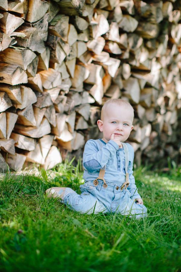 Kind sitzt im Gras vor Holz