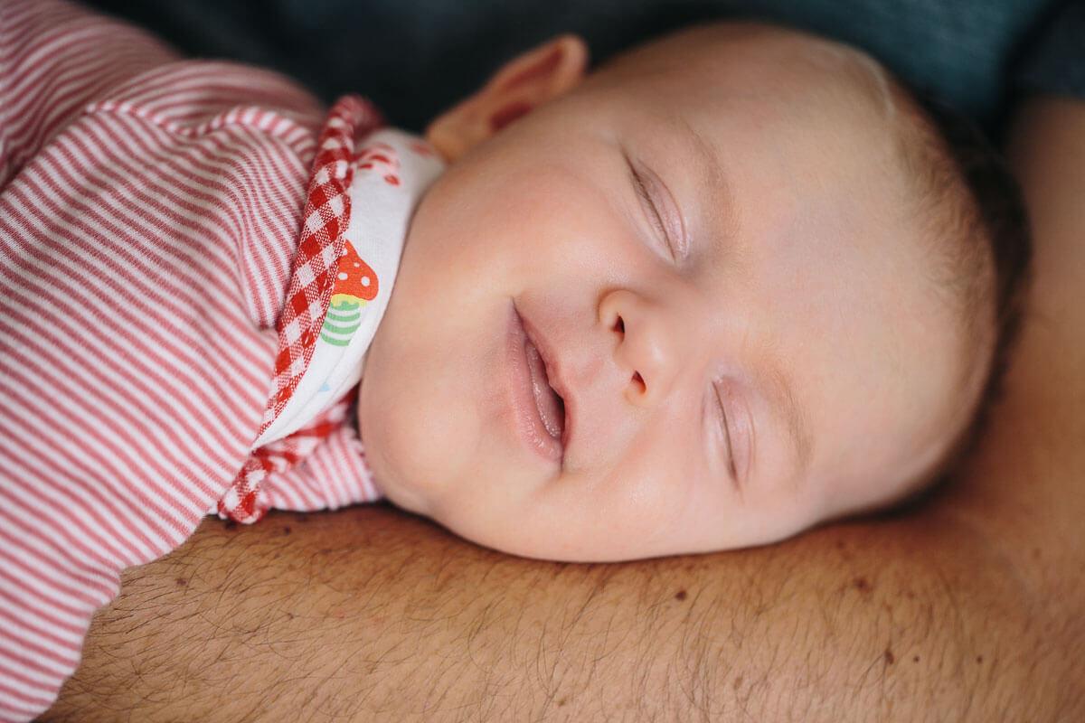 Baby liegt auf Arm und lächelt