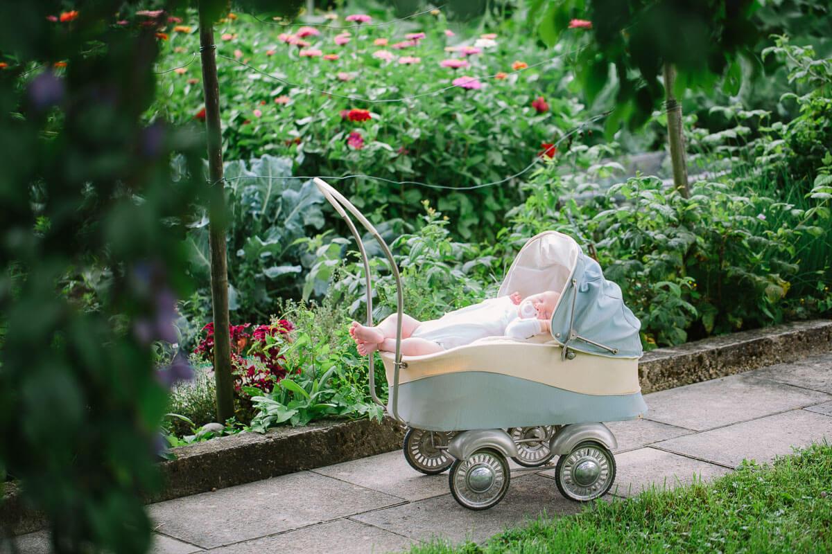 Baby liegt in nostalgischem Kinderwagen
