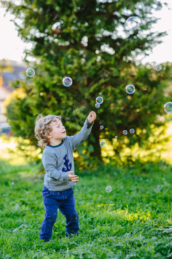 Kind zerstupst Seifenblasen