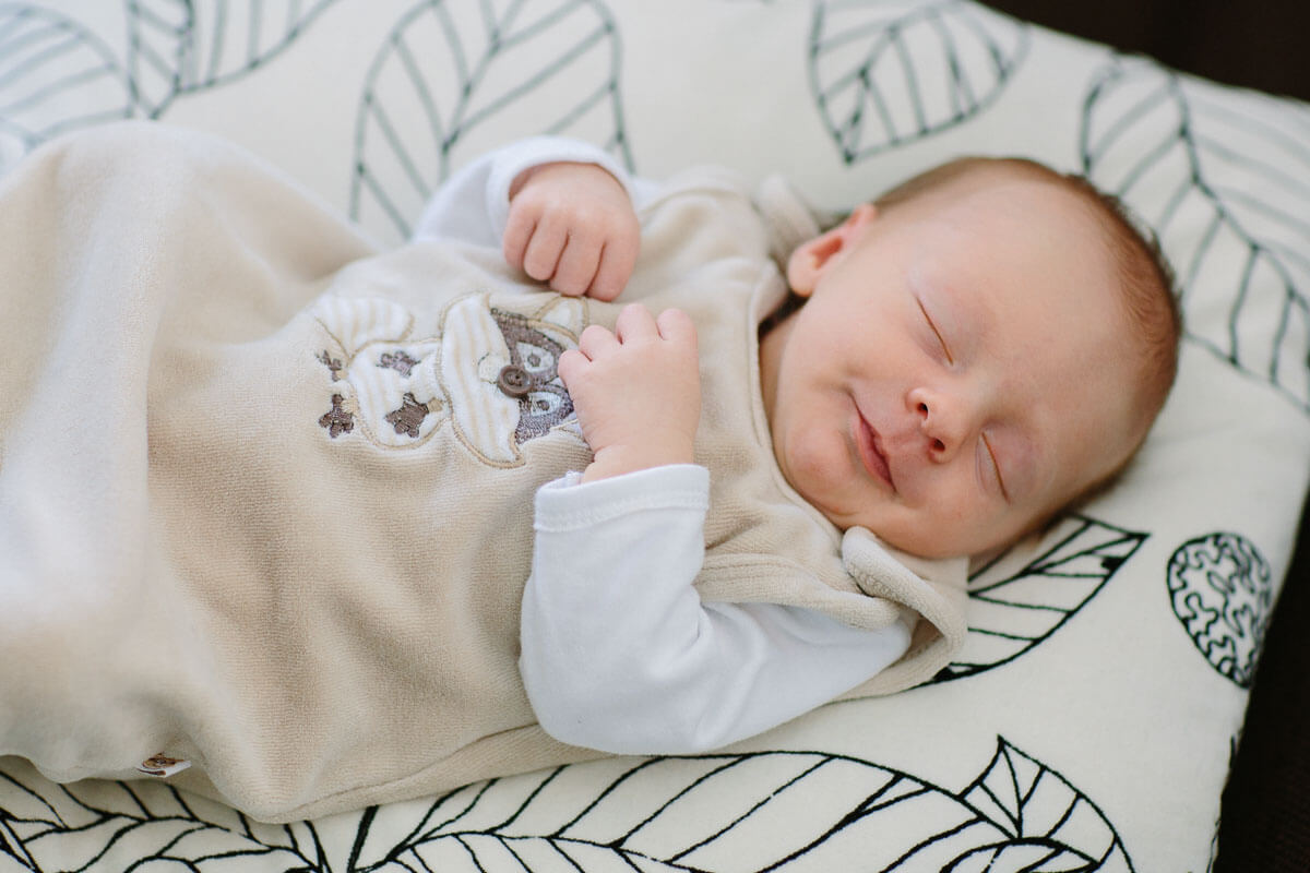 Baby liegt auf Kissen und lächelt