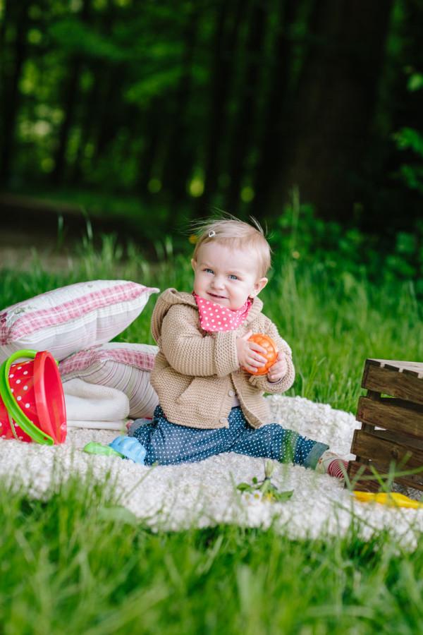 Kind sitzt auf Fell im Wald und spielt