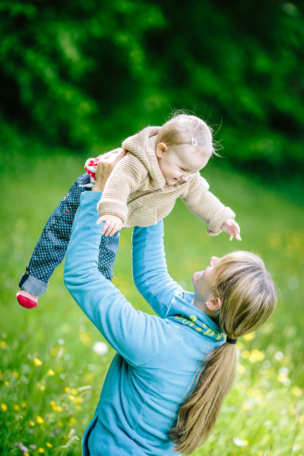 Kind wird von Mutter hochgeworfen und lacht