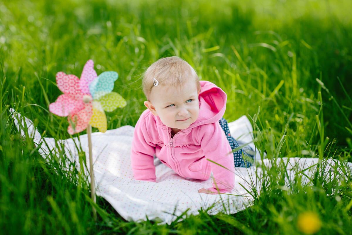 Kind auf Picknickdecke mit Windrad