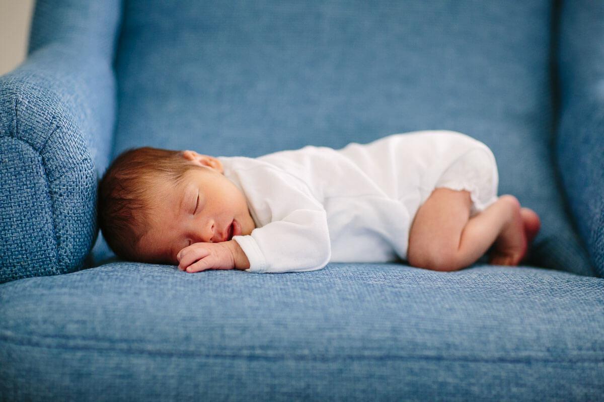 Baby liegt auf blauem Sessel