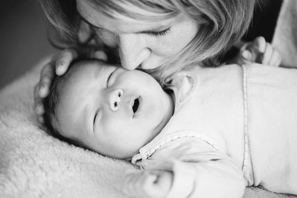 Baby wird von Mama geküsst