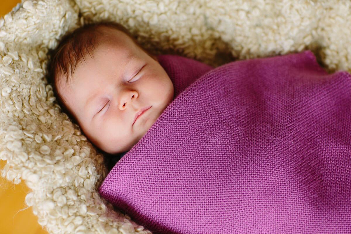 Baby liegt auf Decke und schläft
