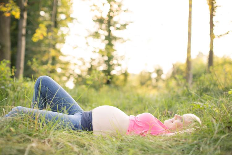 Schwangere Frau liegt im Gras
