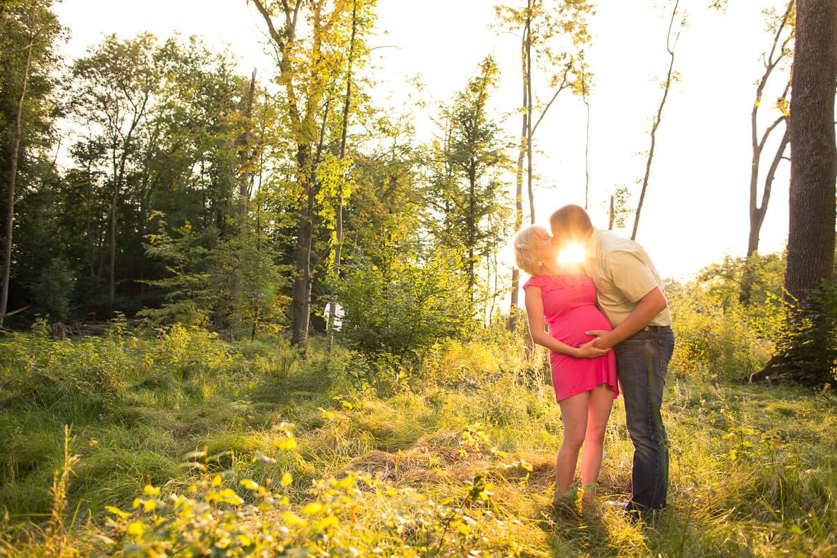 Schwangeres Paar küsst sich, Sonne im Hintergrund
