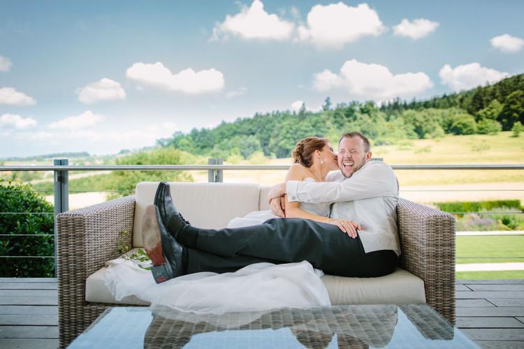 Brautpaar lacht auf Loungesofa, im Hintergrund Natur