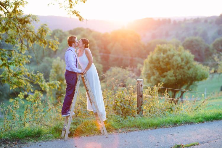 Brautpaar küsst sich auf Leiter, Sonne im Hintergrund