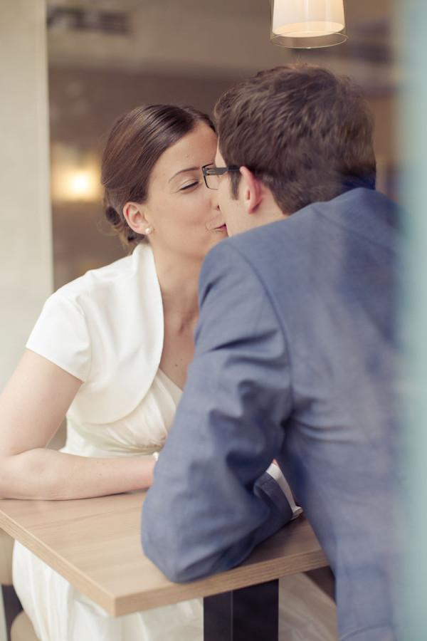 Brautpaar küsst sich in Café