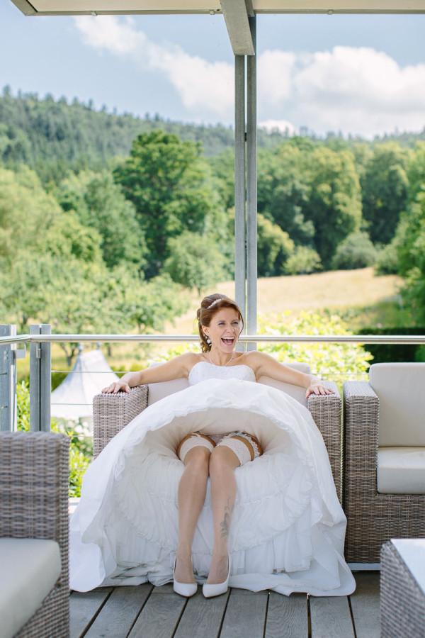 Braut hebt Brautkleid und lacht