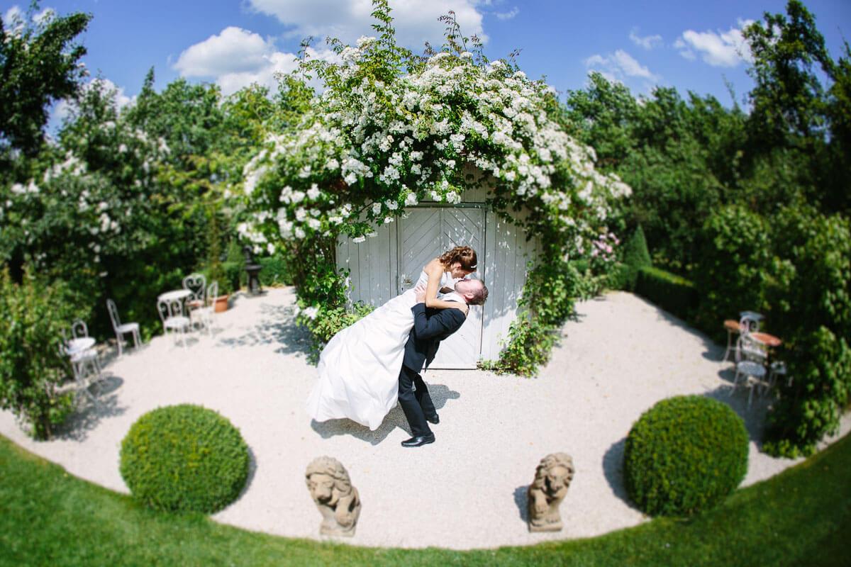 Bräutigam hebt Braut hoch und küsst sie