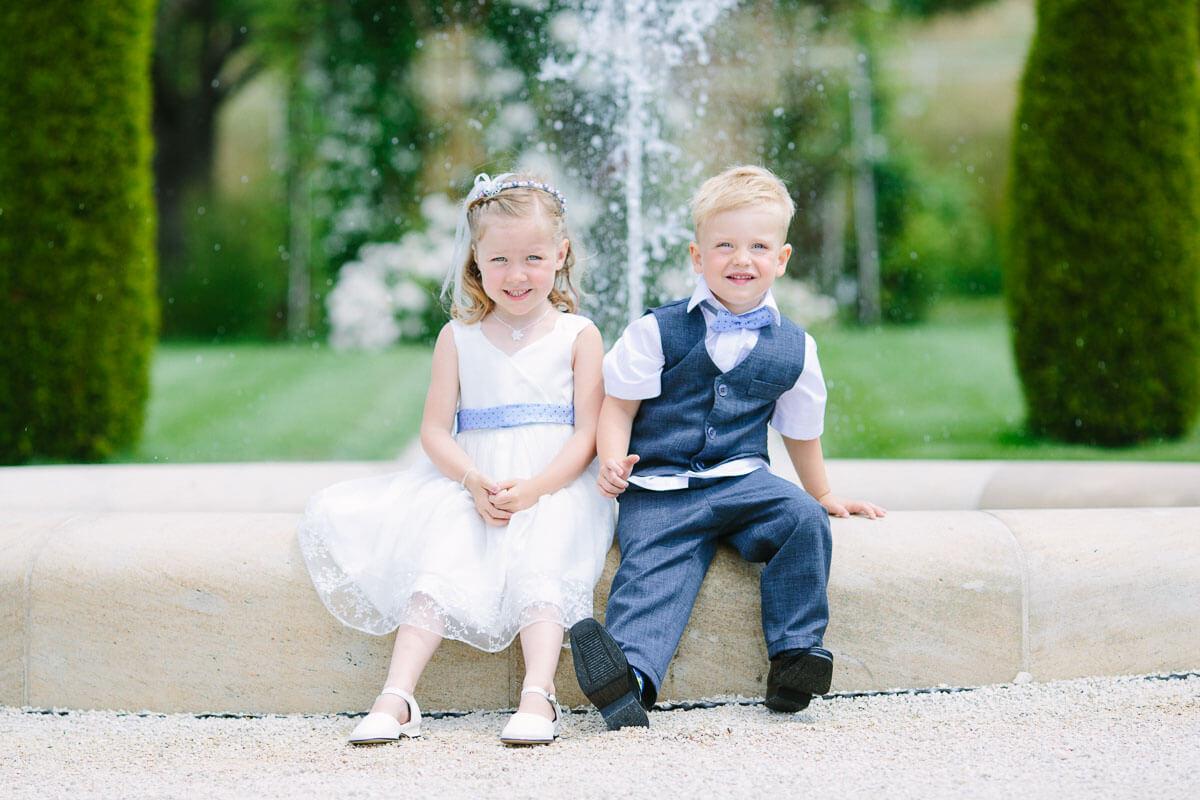 Kinder sitzen an Brunnen