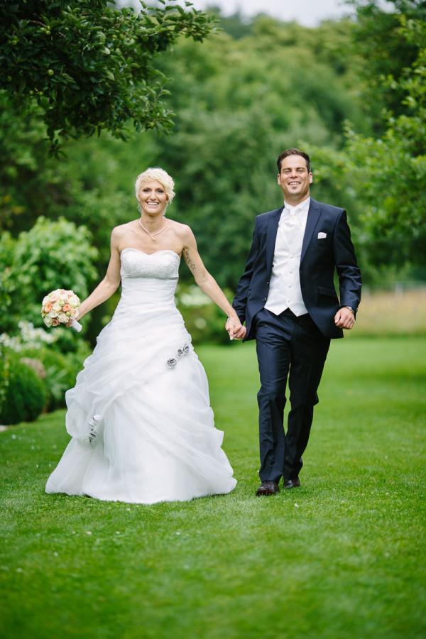 Brautpaar läuft im Gras