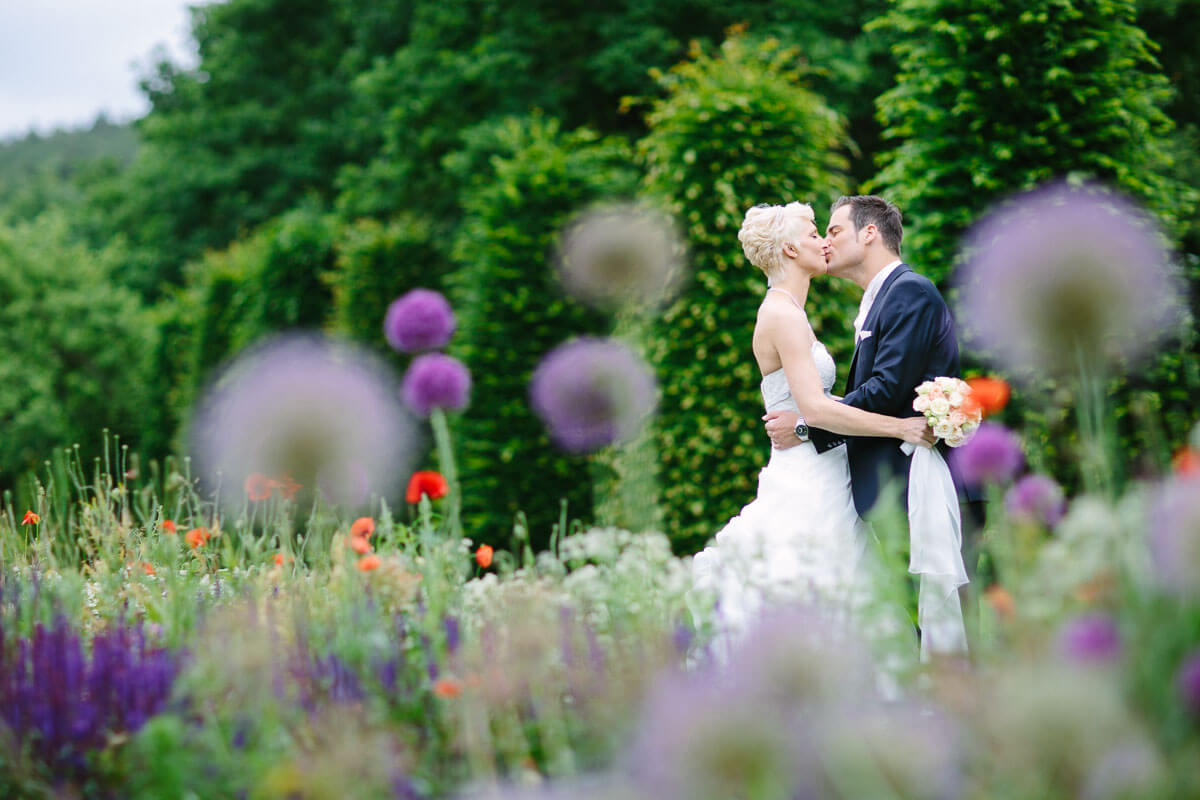 Brautpaar küsst sich mit Blumen im Vordergrund