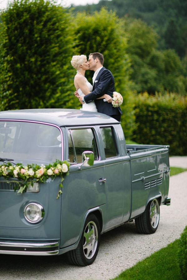 Brautpaar küsst sich auf VW T2 Bus
