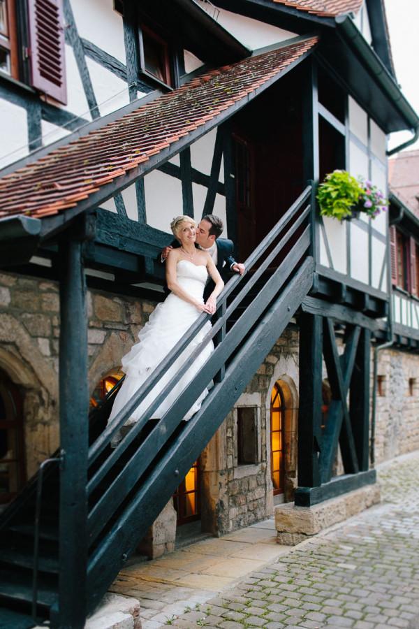 Brautpaar steht auf Treppe von Fachwerkhaus