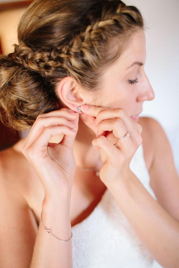 Braut macht sich Ohrringe ans Ohr