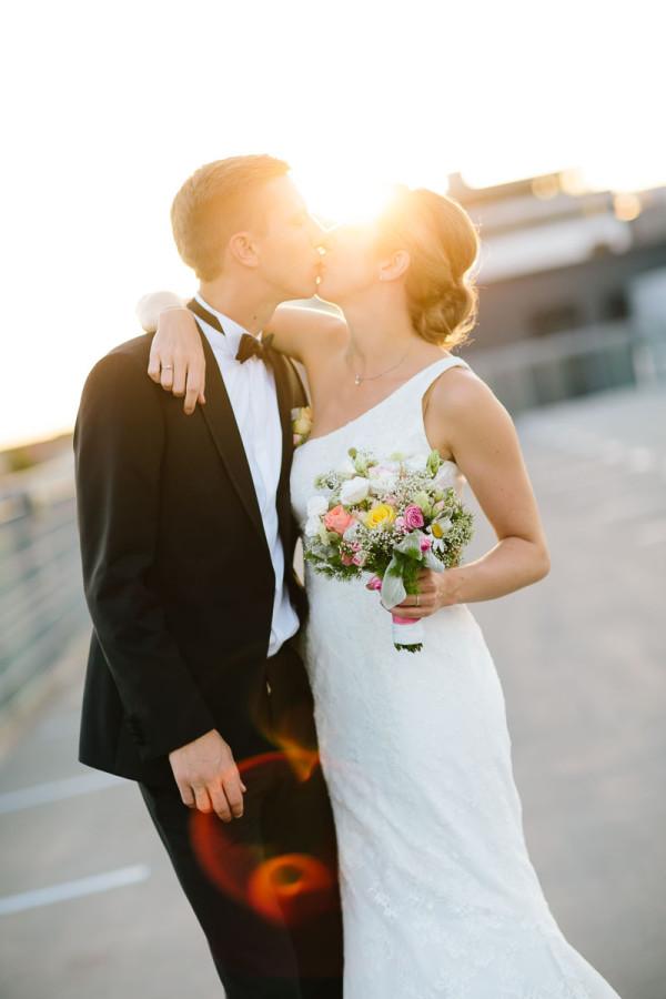 Brautpaar küsst sich auf Parkhausdeck, Sonne im Hintergrund