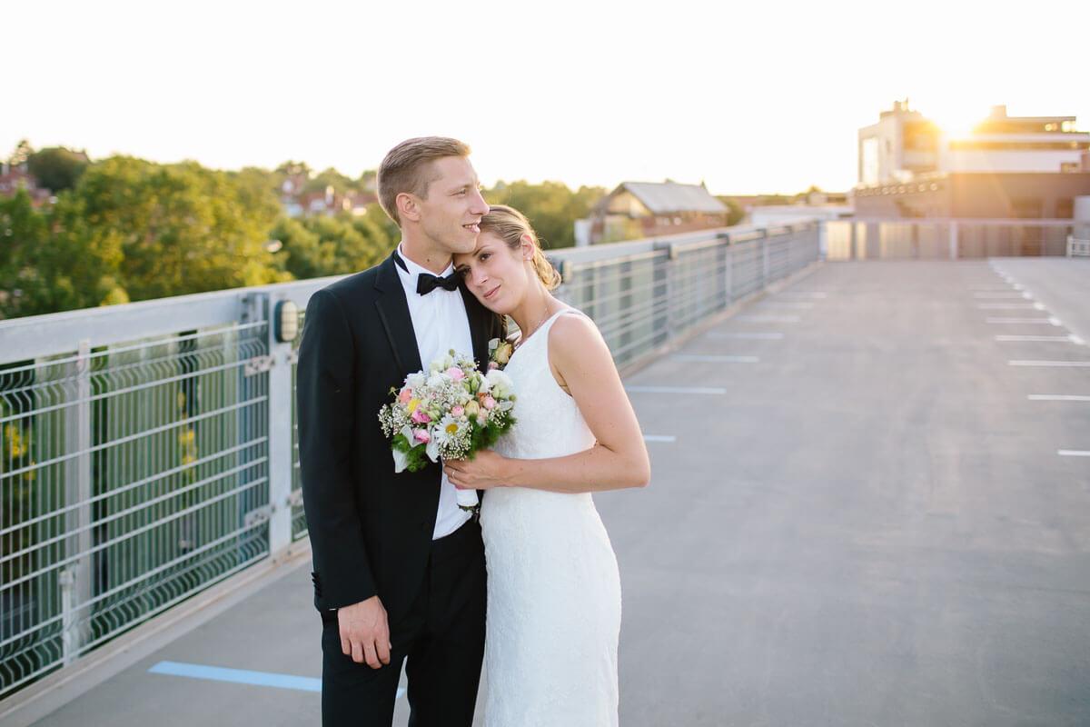 Brautpaar umarmt sich auf Parkhausdeck, Sonne im Hintergrund