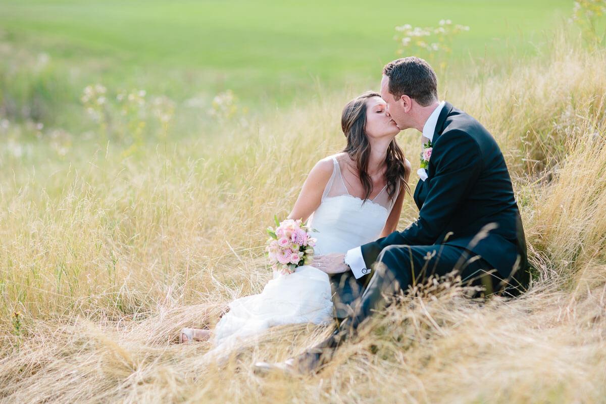 Brautpaar küsst sich im hohen Gras