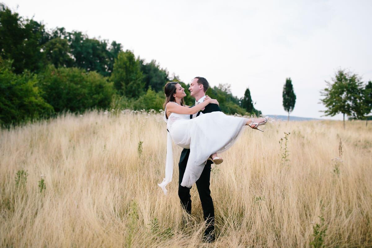 Bräutigam hebt Braut hoch in der Natur
