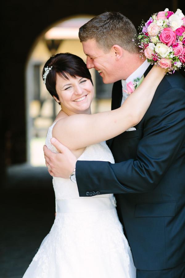 Brautpaar umarmt sich, beide lachen