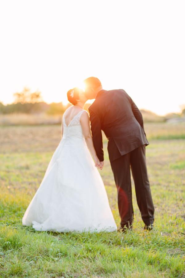 Brautpaar küsst sich, Sonne im Hintergrund