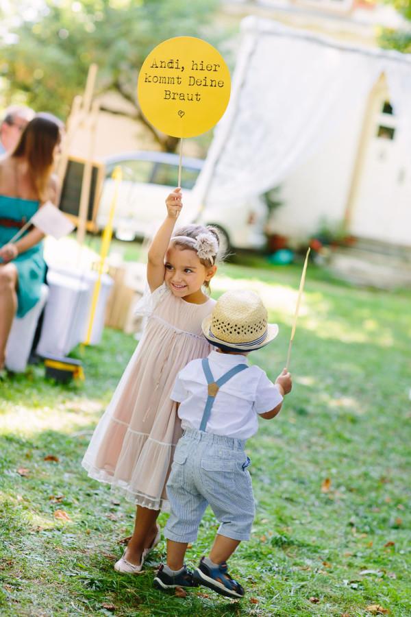 Kinder kündigen die Braut mit Schildern an