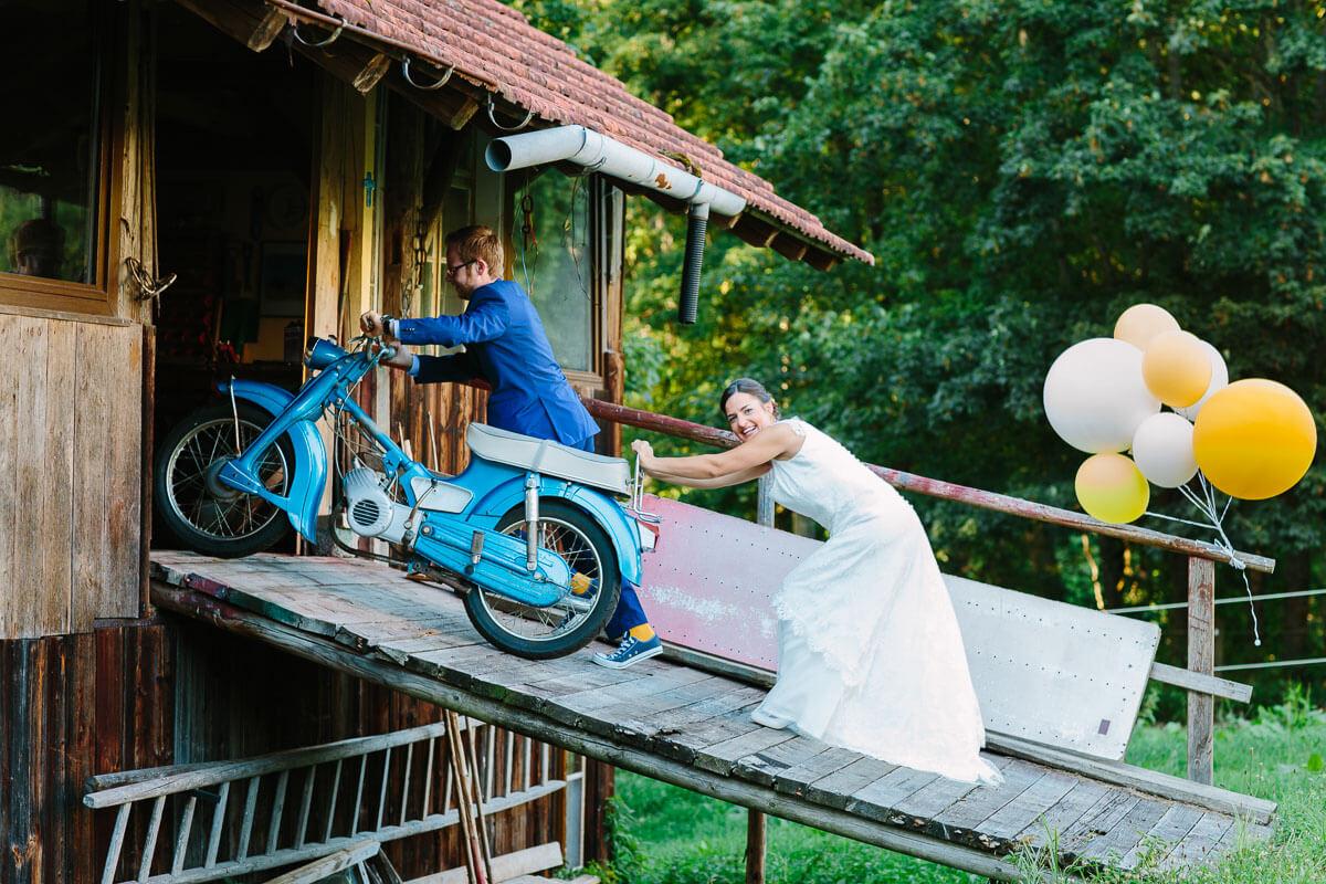 Brautpaar schiebt Moped in Scheune, Braut lacht