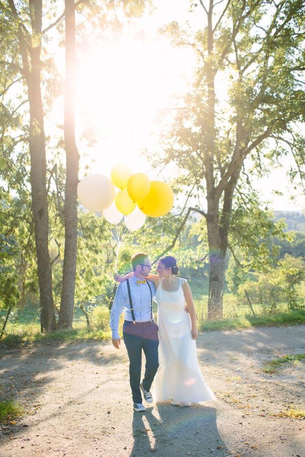 Brautpaar läuft Arm in Arm mit Luftballons, Sonne im Hintergrund