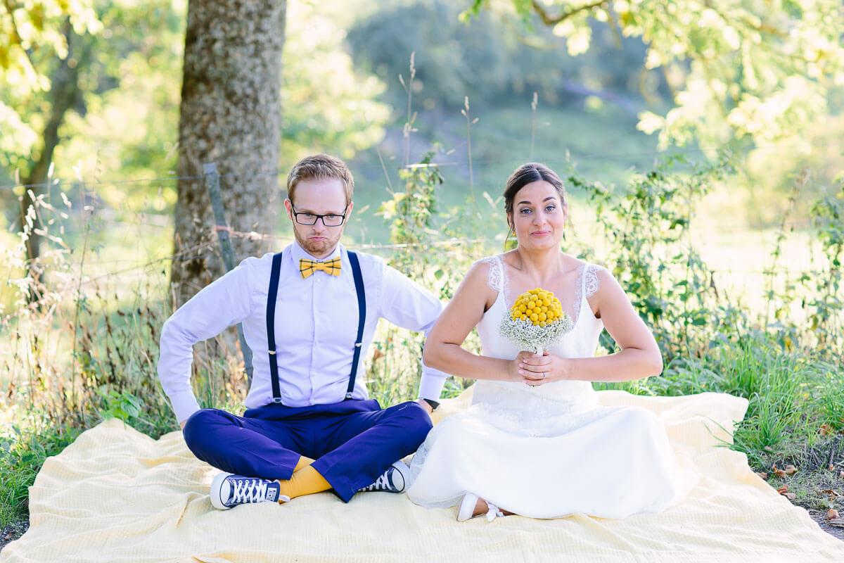 Brautpaar sitzt im Schneidersitz auf Decke