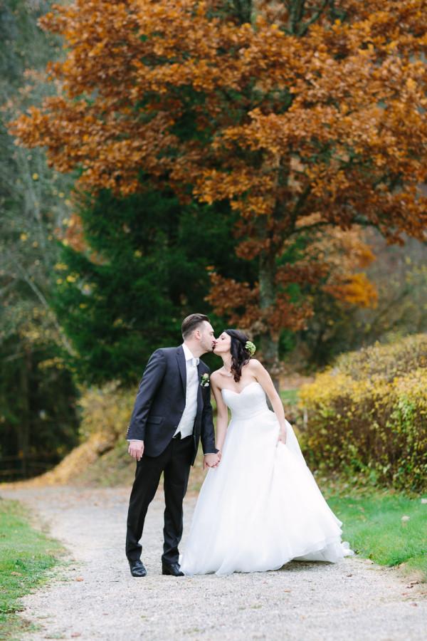 Brautpaar küsst sich im Herbst