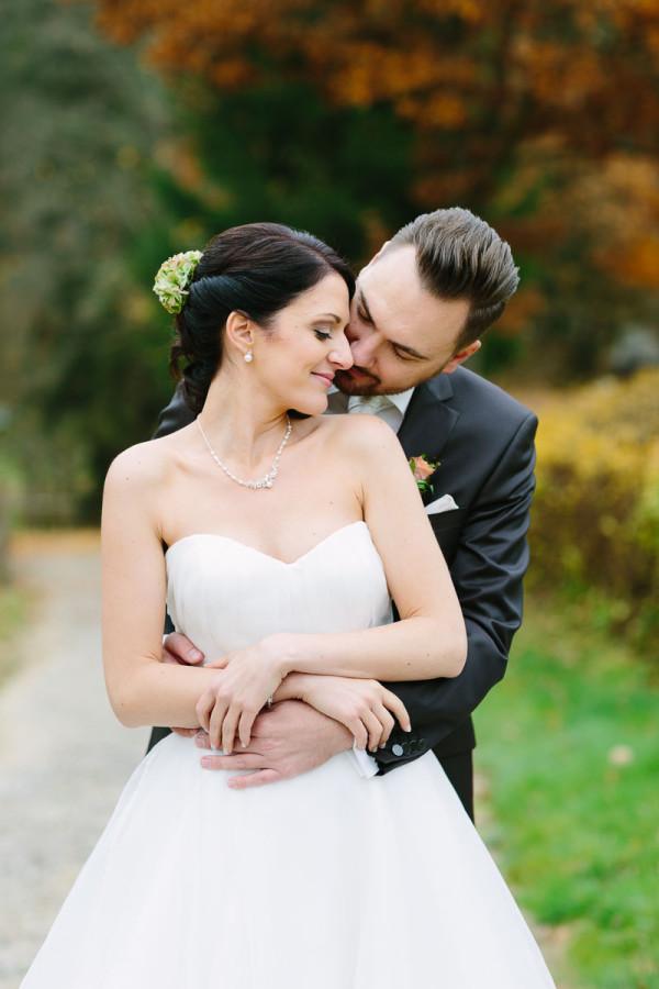 Brautpaar umarmt sich im Herbst