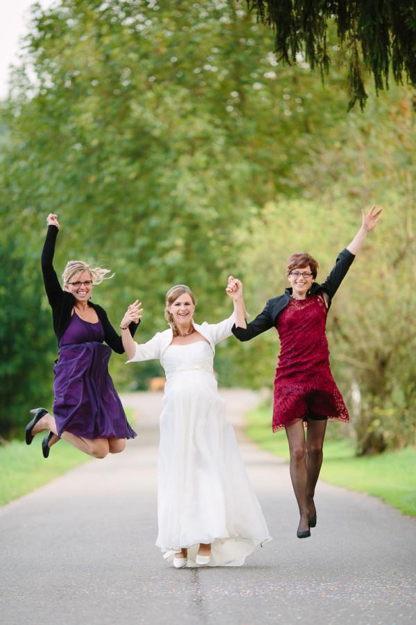Hochzeitsgäste springen mit Braut in die Luft