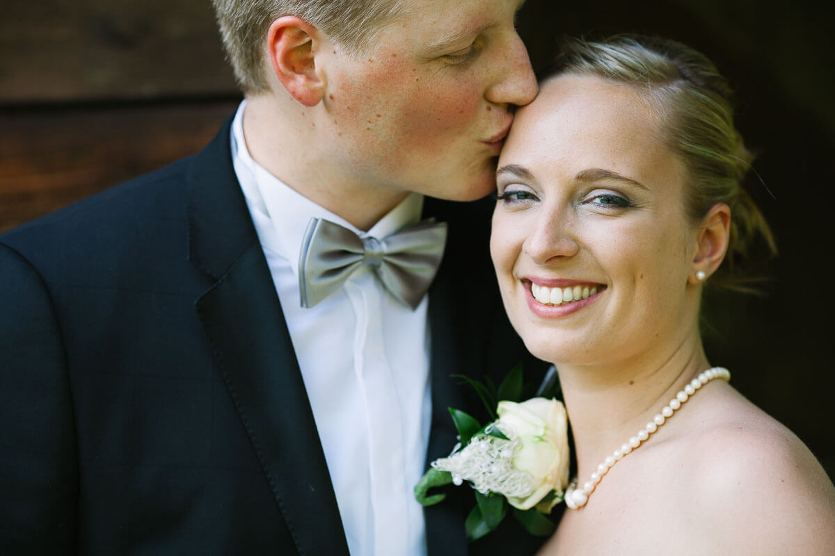 Bräutigam küsst lachende Braut